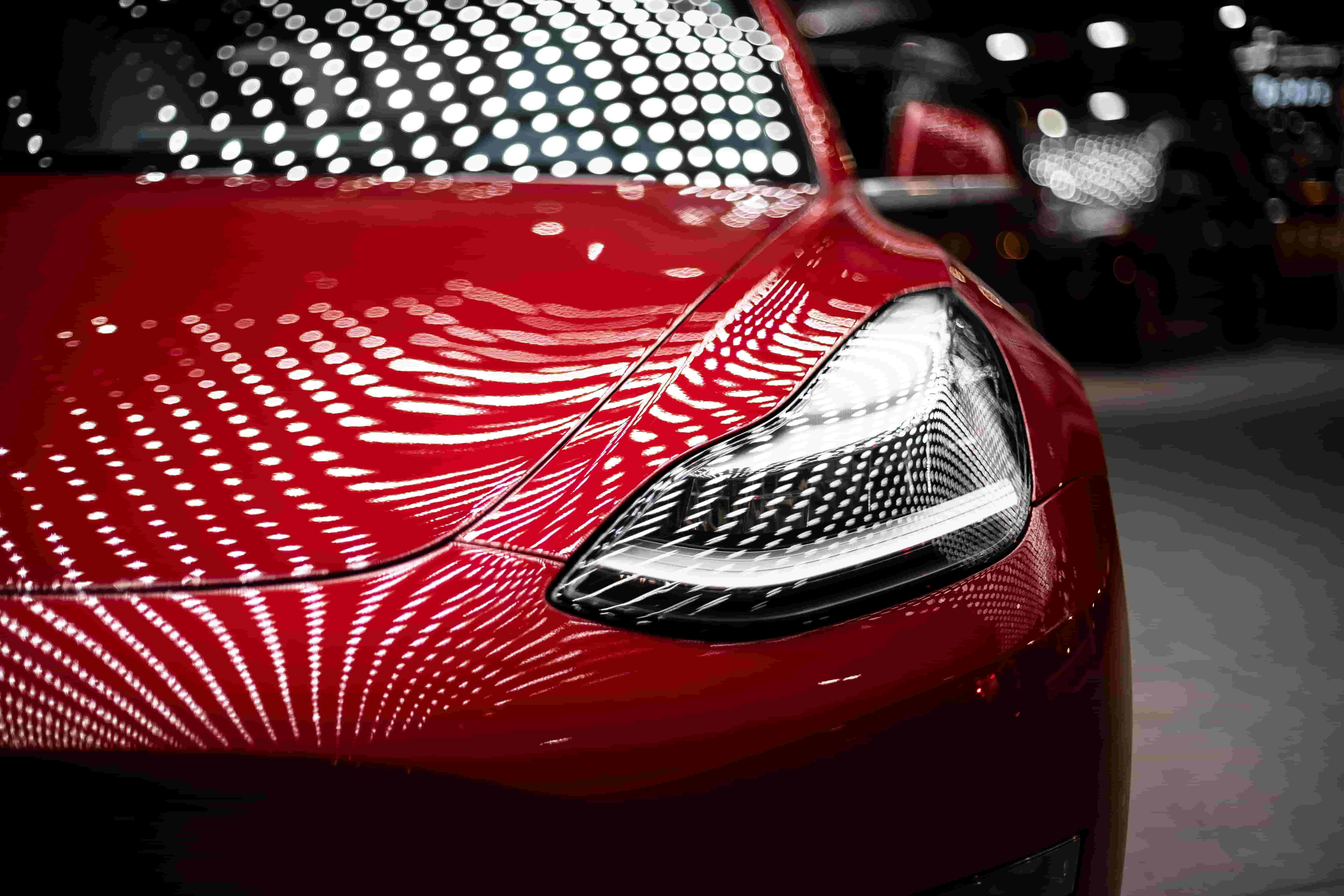 Close-up photo of the hood of a Tesla Roadster, an eco-friendly car.