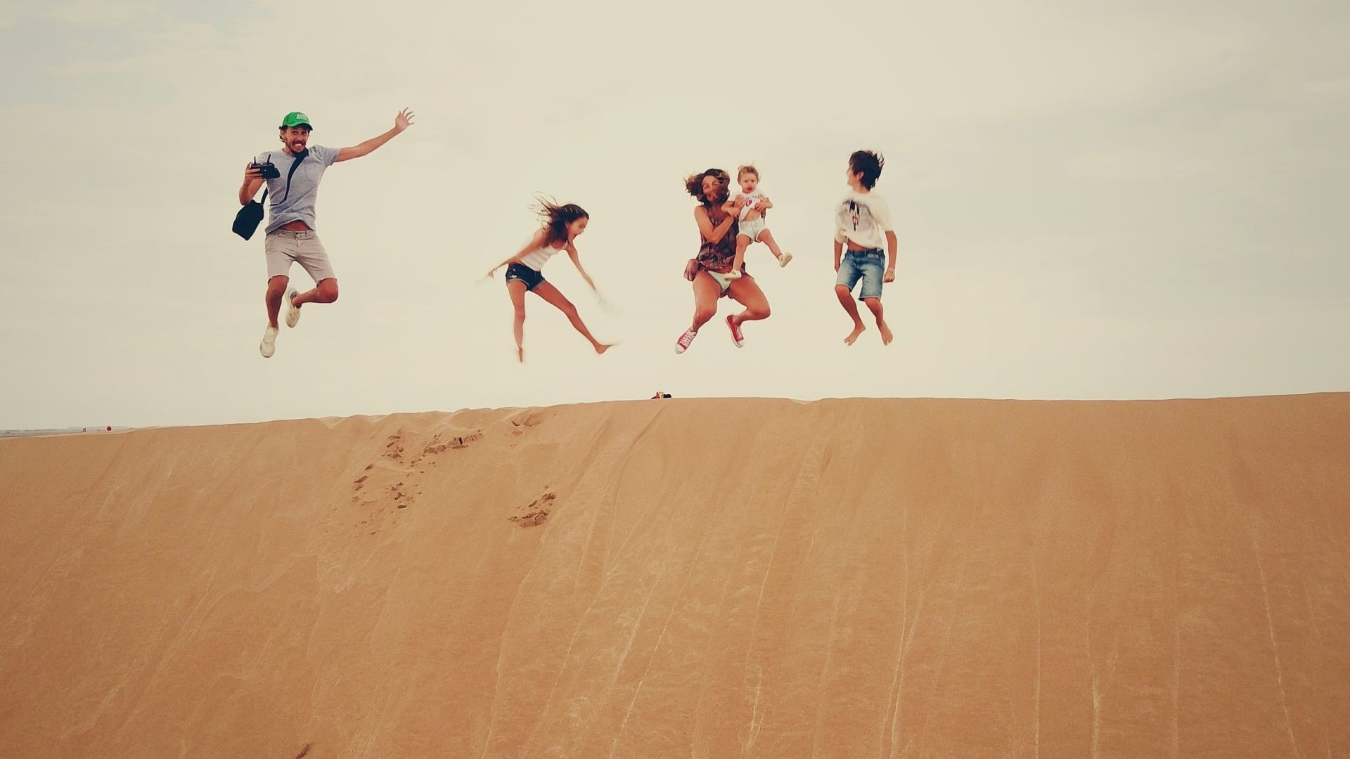 A family on top of a sand dune, jumping in the air.